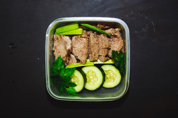 Photo sur Plexiglas Assortiment Boiled beef and pieces of fresh cucumber in a small container on a black background, top view. Healthy food, diet, fitness.