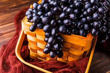 Image of black grapes in wooden basket with claret cloth
