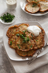 Vegetable pancakes with sour cream on a white plate