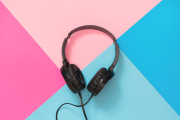 Modern style black headphones on pink blue background.