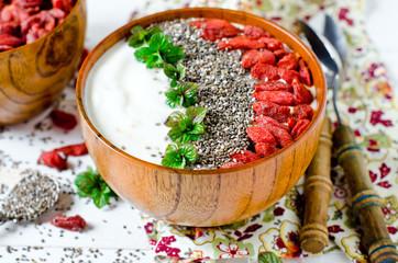 Healthy breakfast yogurt bowl with chia seeds, flax seeds, goji berries