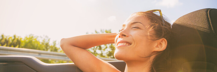 Car road trip summer vacation freedom girl relaxing in sunshine feeling free enjoying sun sitting in convertible sports car in wind banner panorama.