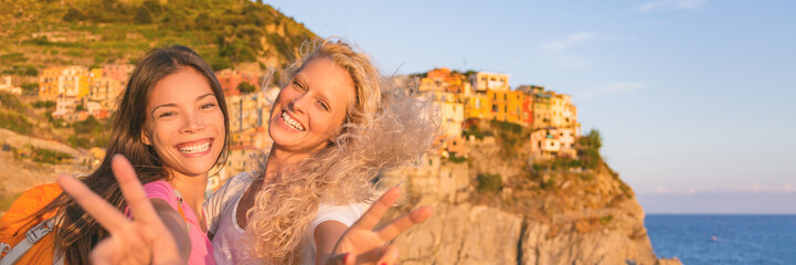 Travel tourists girls friends having fun hiking in Cinque Terre , Italy summer vacation. Happy girlfriends backpacking through Europe laughing banner panorama.