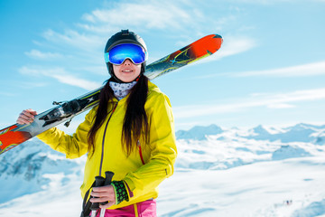 Photo of cheerful girl in helmet and mask with skis