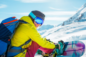 Photo of sporty woman in helmet sitting on snow with snowboard