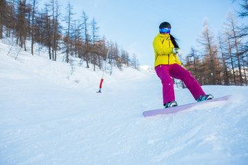 Image of female athlete wearing helmet and mask snowboarding from snowy slope with trees