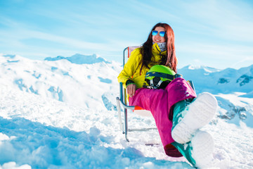 Photo of sports long-haired brunette with helmet resting on armchair in winter resort during day