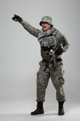 Full-length picture of military man in helmet with hand pointing