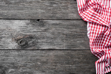 Red checkered textile on rustic wood. Food background
