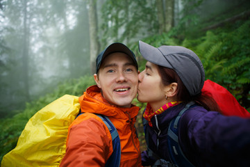 Photo of girl kissing guy with backpack