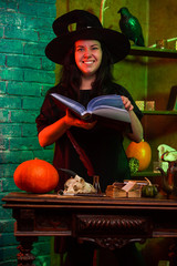 Portrait of witch with book at table with pumpkin, skull