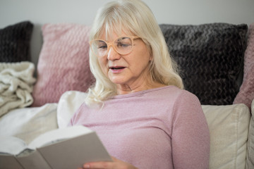Senior lady at home reading book intently