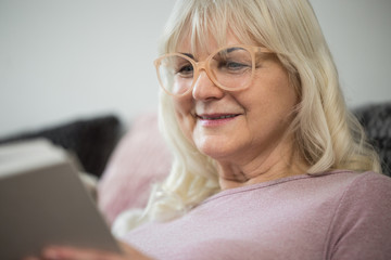 Happy senior woman in glasses reading book