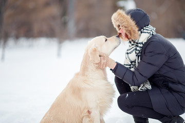 Picture of girl in black jacket embracing labrador in snowy park