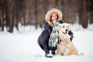 Photo of girl in black jacket squatting next to dog in winter