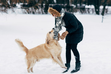 Photo of woman in black jacket with retriever walking in winter park