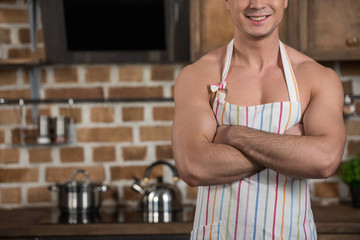 cropped image of smiling sexy shirtless man standing with crossed arms in apron