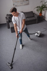 high angle view of handsome man cleaning living room with vacuum cleaner