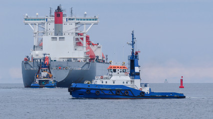 MARITIME TRANSPORT - LNG tanker flows into sea secured by tugs