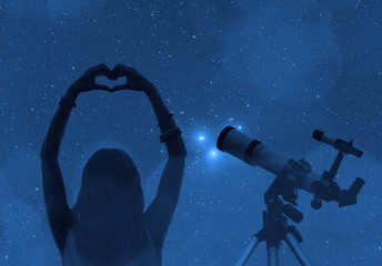 Girl holding a heart - shape with telescope and stars.