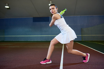 Full length portrait of confident young woman playing tennis in indoor court, ready to hit flying ball, copy space