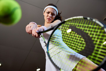 Low angle portrait of forceful woman playing tennis in indoor court, focus on tennis racket hitting ball, copy space