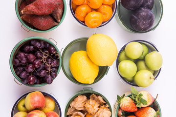 Close up of bowls of various kinds of fruits laying over white background - creative health concept