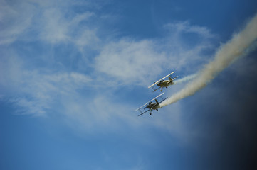 Two vintage single engine propeller biplanes aircrafts flying away and smoking