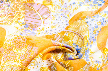 Texture, background, pattern. Blue silk fabric, yellow flowers. Silk scarf with flowering flowers in blue and yellow colors. Collection of retro textile design. Autumn colors.