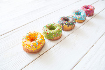 Set of donuts on white wooden background