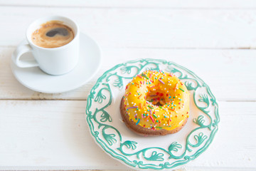 Yellow donut and coffee on wood background