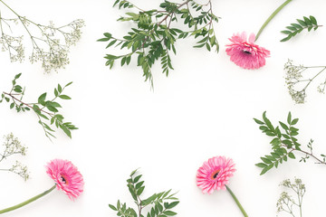 Pink flowers, green leaves, on white background, flat lay, top view