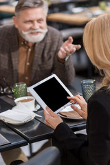 cropped shot of businesswoman using tablet during meeting with colleague in cafe