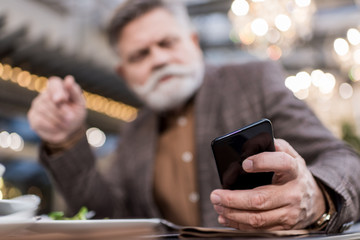 selective focus of businessman using smartphone in cafe