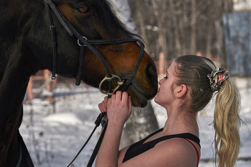 A girl with long blonde hair communicates with her favorite horse. The girl loves animals. Sunny spring day. Close-up.