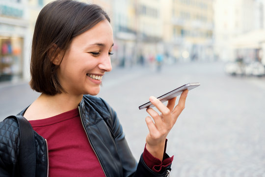 Young woman using vocal assistant and sending vocal message