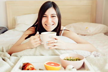 Breakfast in bed / beautiful brunette woman holding white porcelain cup in hand and smiling lying in bed