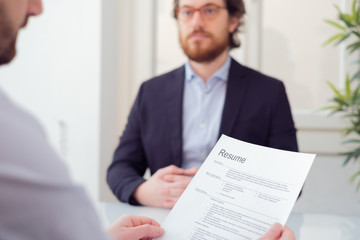Recruiter reading curriculum of a candidate for a job , main focus on the resume application
