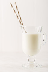 Glass of milk with two paper drinking straws on white background