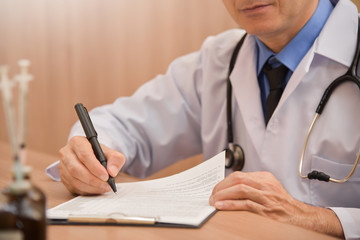 Asian male doctor is writing something on clipboard.
