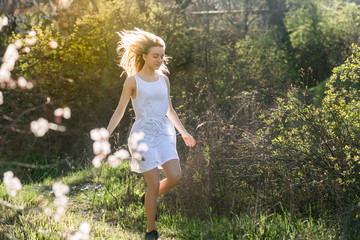 Teenage girl in white dress is running in the spring garden