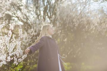 Blonde teen girl enjoying in the spring garden