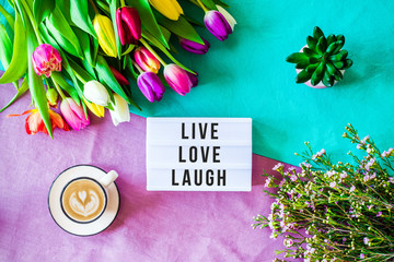 Live love laugh written in lightbox with spring flowers from above
