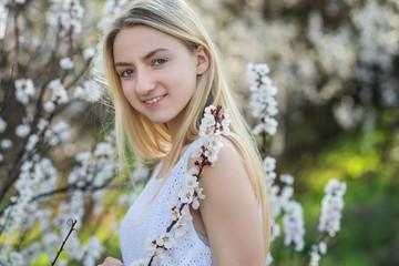 Teenage girl in blooming apricot garden