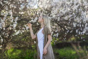 Teenage girl inhales aroma of flowering apricot trees in the garden