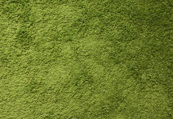 Green carpet. Surface imitating green grass. A close-up photograph. Top view