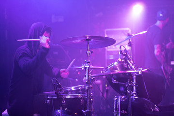 Rocker drummer is playing on stage.