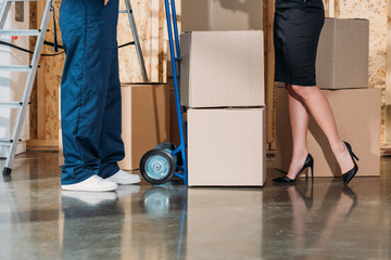 Businesswoman and delivery man standing by stack of cardboard boxes