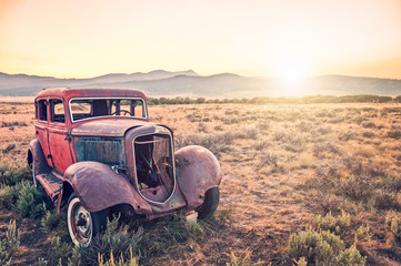 Old rusty antique car, abandoned in a field at sunset