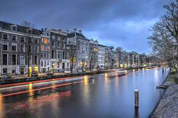 View at dusk of Nieuwe Herengracht canal in downtown Amsterdam with houses on one side and a park with trees on the other side